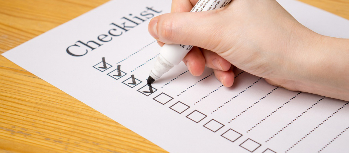 person checking off items on checklist with pen